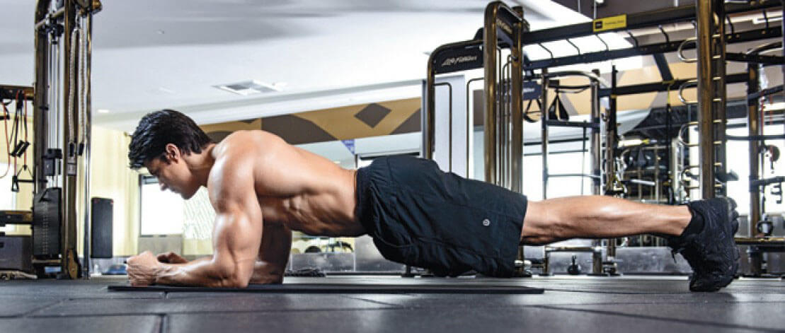 young bodybuilder working out plank